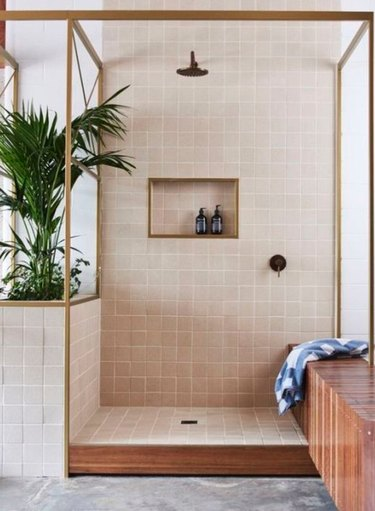 Plants and natural wood accents give a breezy island feel to this shower.