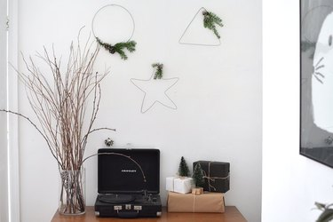 Christmas wire wreaths hanging on wall with holiday decor.