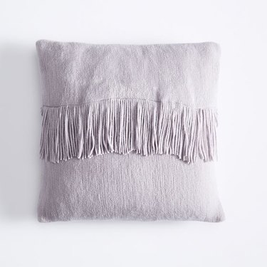 purple throw pillow with fringe detail
