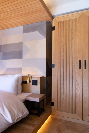 Wood closet design with geometric accent wall and modern bedroom accents
