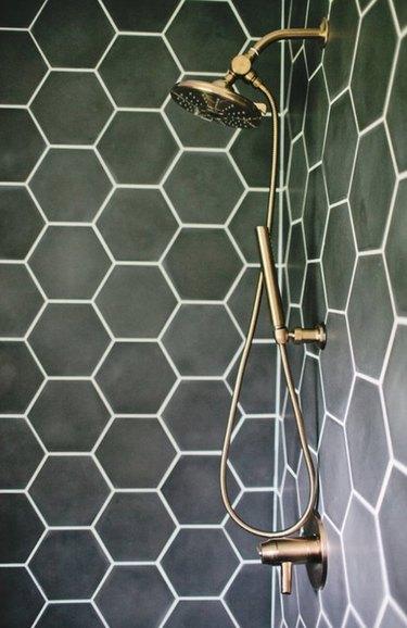 Moss green hexagon shower tiles with brass fixtures.