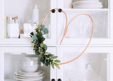 Copper pipe heart wreath with eucalyptus hanging on cabinet door.