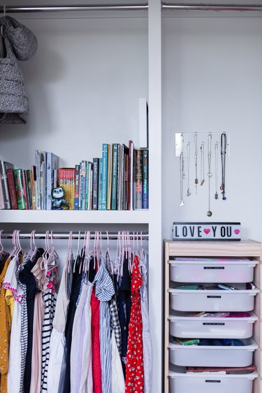 Kids' closet design with plastic bins, books, and hanging clothes