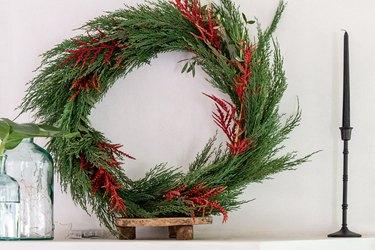 Faux holiday wreath with cedar on mantel.