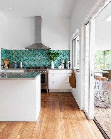 teal kitchen idea with chevron pattern tile backsplash and white cabinets