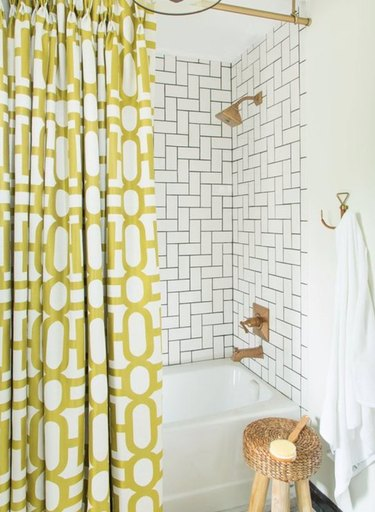 Subway tiles in a mix and match pattern in shower with yellow modern shower curtain.