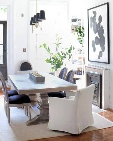 dining room table centerpiece with slipcovered chairs with black french louis dining chairs in neutral dining room
