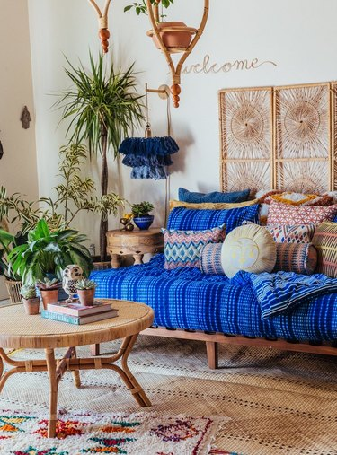 daybed in the living room idea with a wood daybed with a thick blue cushion and lots of throw pillows