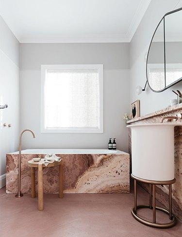contemporary bathroom with rosy marble bathtub surround