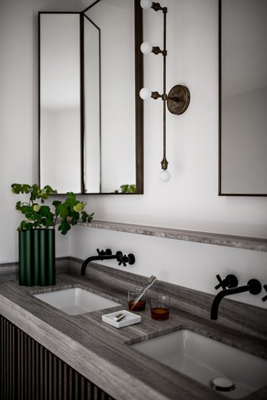 masculine bathroom with his and hers sinks and black wall mount faucets