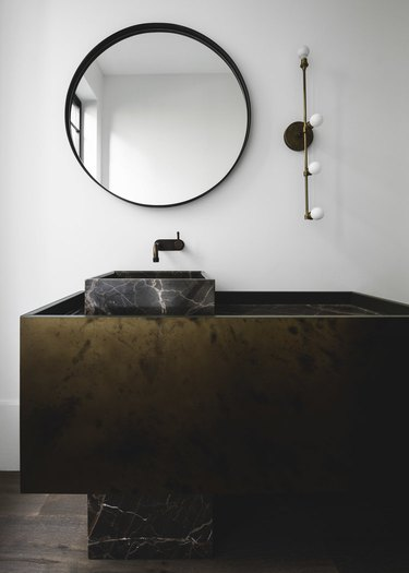 contemporary bathroom with black marble and metal vanity and wall mount faucet