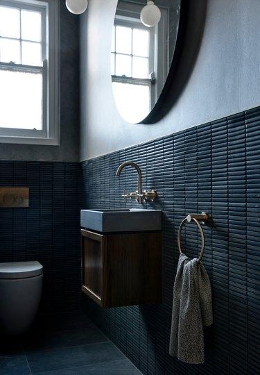 moody bathroom with gray walls and dark wall tile
