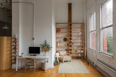 view of minimalist office and bookcase, hardwood floors and wall of windows