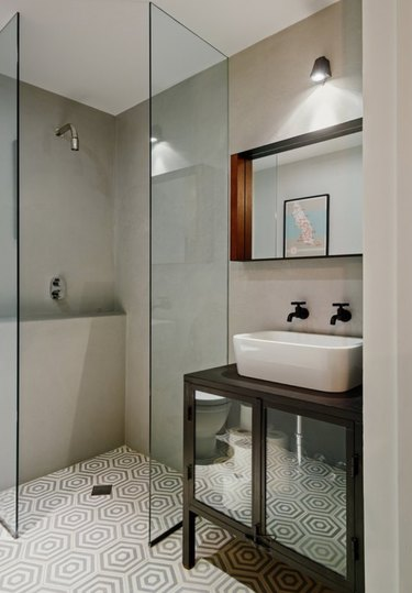 Frameless and doorless shower in bathroom with cement hexagon tile.