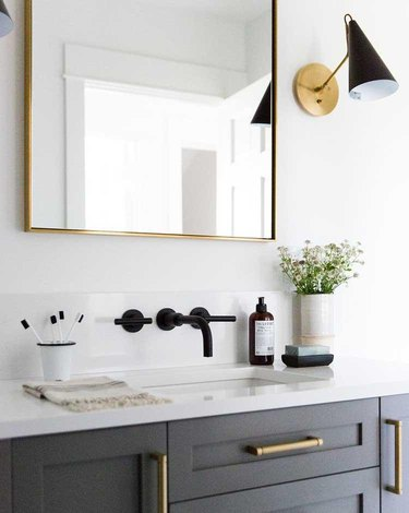 white bathroom countertop with gray cabinets and brass hardware and black fixtures
