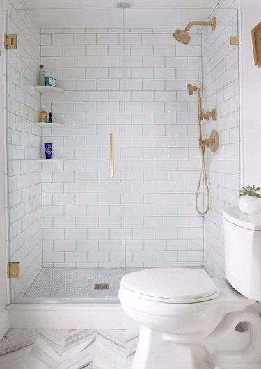 Brass hardware in shower with frameless door and white tile.