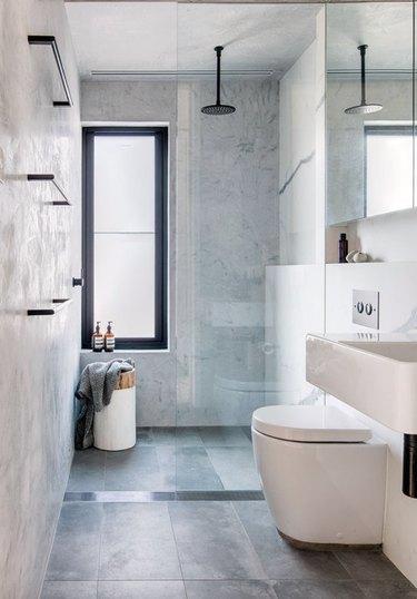 Modern bathroom with black fixtures, frameless shower door, and light gray floor tile.