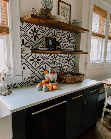 Black and white Mexican tile backsplash with open shelving and decorative pieces