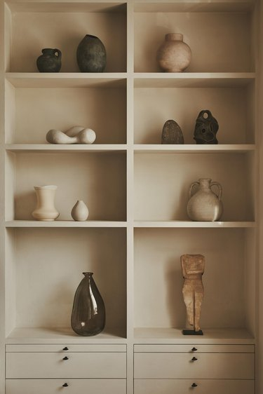 bookcase styled with ceramics and art objects