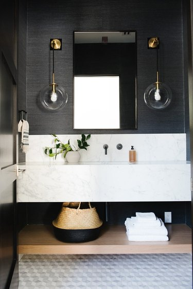 black powder room with floating vanity and bistro wall sconces