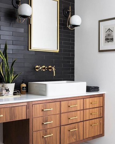 white bathroom countertop with warm wood vanity cabinet and black tile backsplash