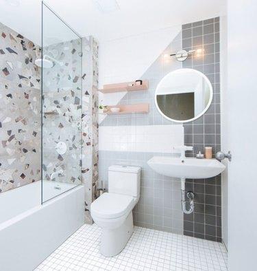 Terrazzo tile shower walls with while bathroom floor tiles and frameless shower door.