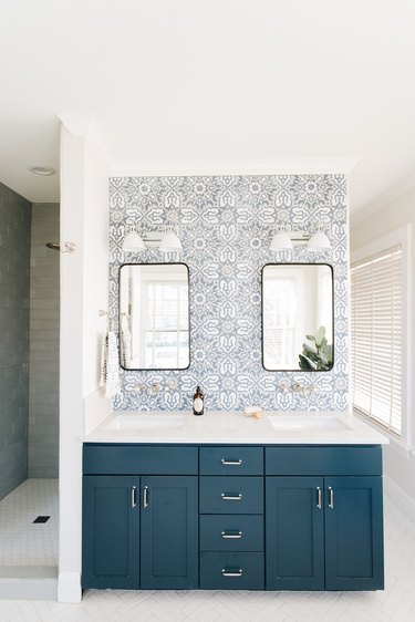 white bathroom countertop with blue cabinets and blue and white patterned backsplash