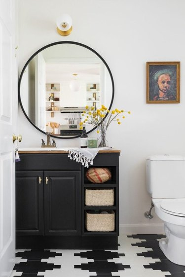 white half bathroom idea with black vanity cabinet and patterned tile flooring