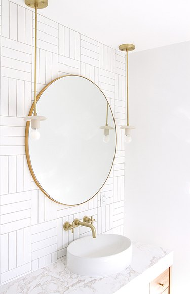 white half bathroom idea with brass fixtures and round vessel sink