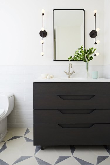 white half bathroom idea with black vanity cabinet and patterned floor tile