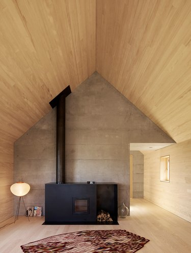 black metal fireplace with chimney and wood storage