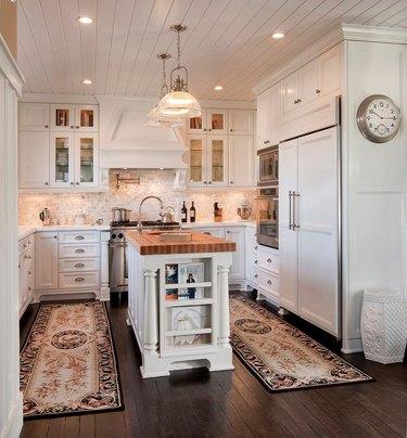 travertine backsplash in traditional white kitchen
