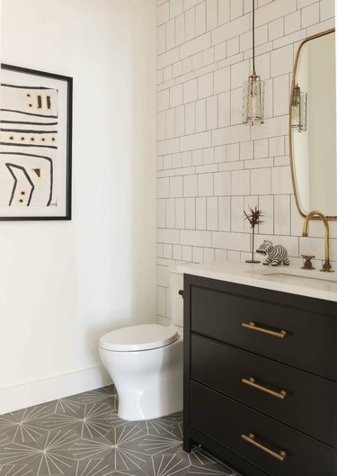 half bathroom idea with black cabinet and patterned tile floor