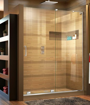 Brown and gold tiles in large modern shower with frameless shower door.