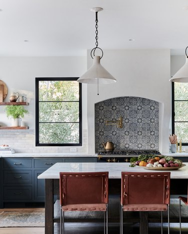 Mexican tile backsplash above oven range in open kitchen with island