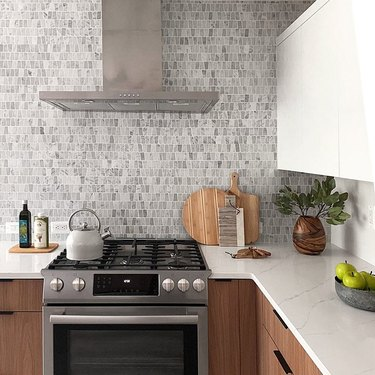 marble mosaic kitchen backplash with wood cabinets and marble countertops exposed hood