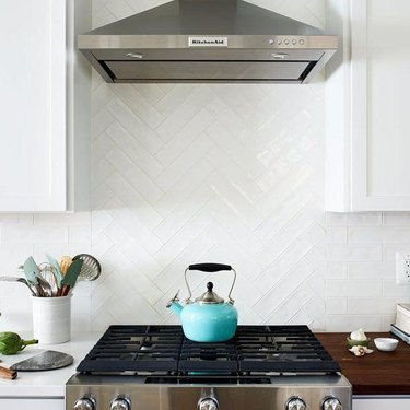 white herringbone pattern subway tile as stove backsplash