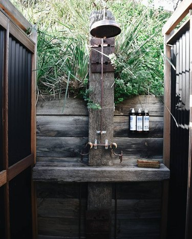 Rustic shower idea with reclaimed wood, worn plumbing fixtures, and plants