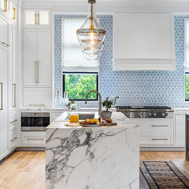 blue tile backsplash modern marble waterfall kitchen with white cabinets and brass hardware