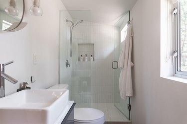 Modern white bathroom with frameless shower door.
