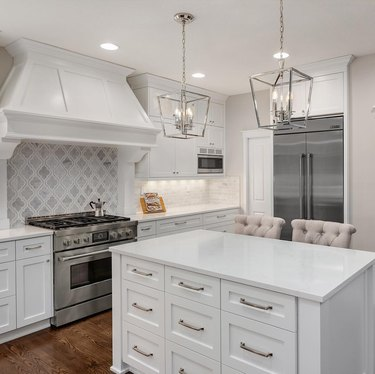 neutral traditional kitchen with arabesque marble backsplash and white countertops