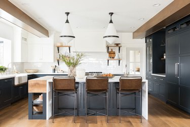navy blue kitchen color idea with blue cabinets and island and wood ceiling beams