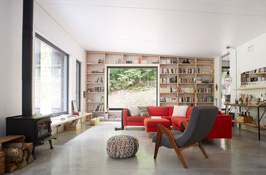 contemporary living room with bookshelves, big windows and wood stove fireplace