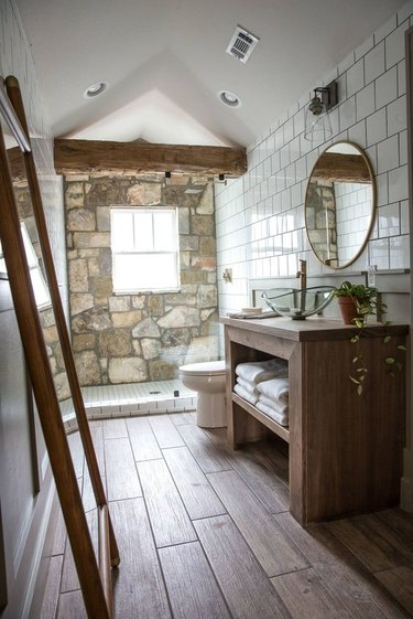 rustic shower idea with exposed wood beam and stone accent wall