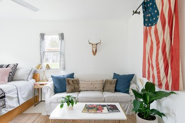 living room space with couch, pillows, and American flag hanging nearby