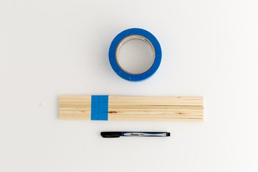 Tape the dowel rods together and mark the line where they need to be cut.