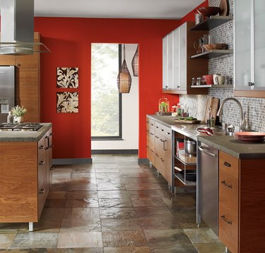Red painted accent wall in kitchen with wood cabinetry and slate floors.
