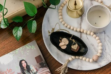 Black air-dry clay dish with jewelry on marble tray.