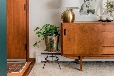 Basket with green and red tassels next to wood credenza with brass lamp.
