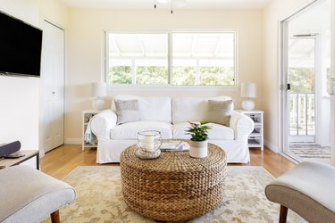 living room space with white couch and woven ottoman